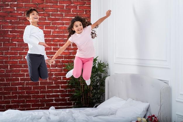 Игривая детская прыгает в постели Бесплатные Фотографии