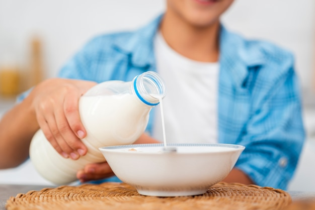 穀物の上に牛乳を注ぐクローズアップ少年 無料写真