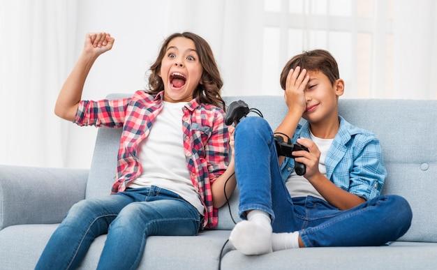 ジョイスティックで遊ぶ若い兄弟 無料写真