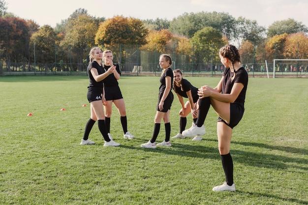 サッカーのフィールドでウォーミングアップの女性 無料写真