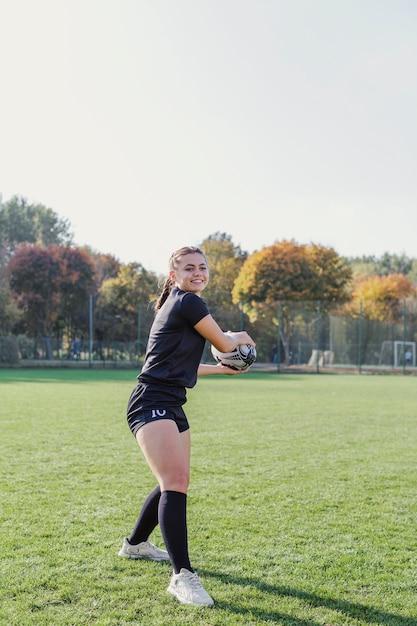 ラグビーボールを保持している陽気な少女 無料写真