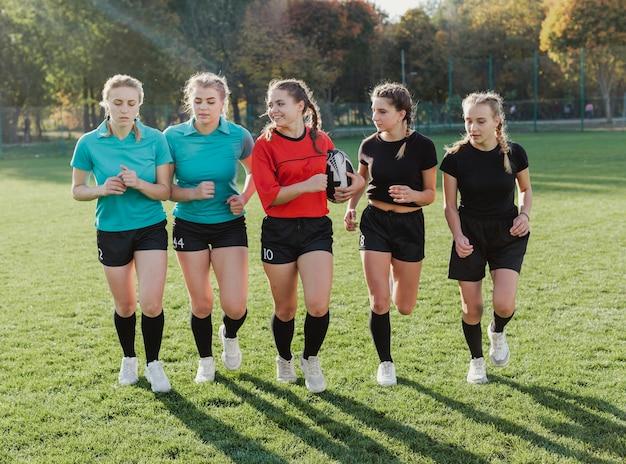 ボールで実行されている女性のラグビーチーム 無料写真