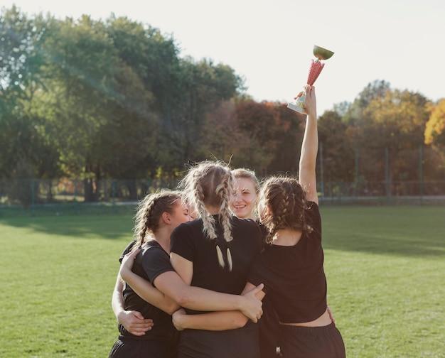 スポーツトロフィーを抱きしめて保持している女性 無料写真