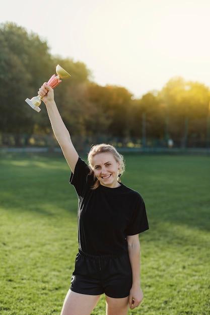 トロフィーを上げるかなりブロンドの女性 無料写真