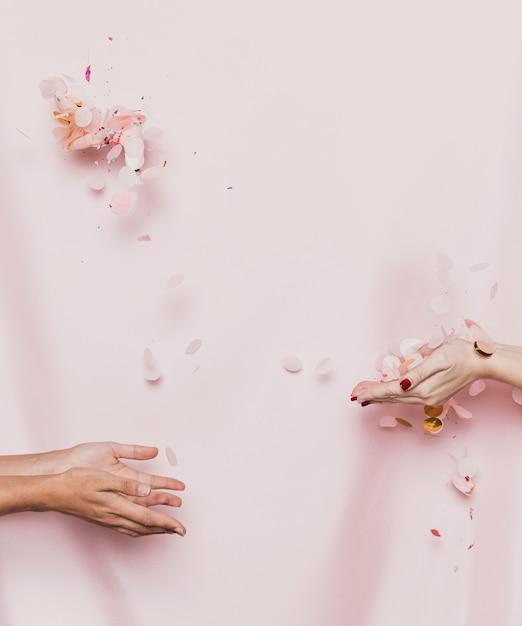 繊維の背景を持つ花びらを投げている手 無料写真