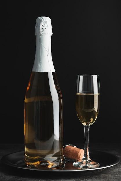 Бутылка шампанского с бокалом на подносе Бесплатные Фотографии