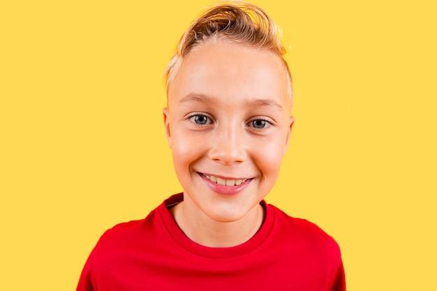 黄色の背景に笑みを浮かべて肖像若い男の子 無料写真