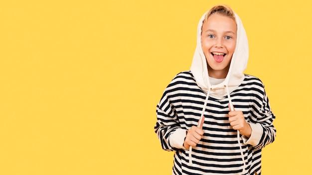 パーカーを着て舌を持つ少年 無料写真