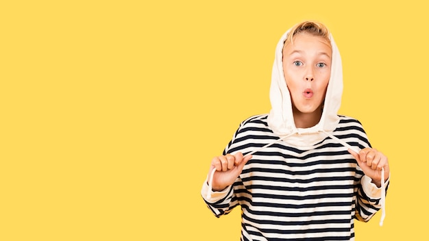 黄色の背景にパーカーを着て遊び心のある少年 無料写真