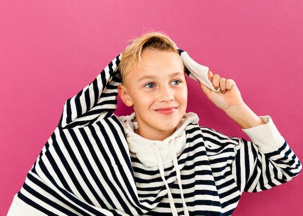 身に着けているパーカーで遊ぶ少年 無料写真