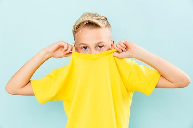 Мальчик вид спереди стягивая свою футболку Бесплатные Фотографии