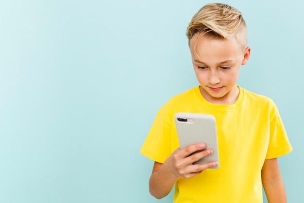 コピースペースで電話を使用してフロントビュー少年 無料写真