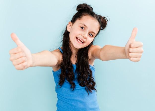 Девушка вид спереди показывает знак ок обеими руками Бесплатные Фотографии