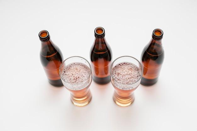 ビール瓶と白い背景の上のグラスが並んで 無料写真