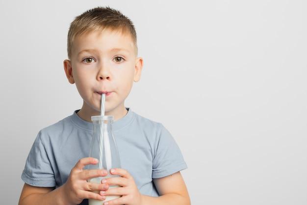 ストローで瓶の中の牛乳を飲む少年 無料写真