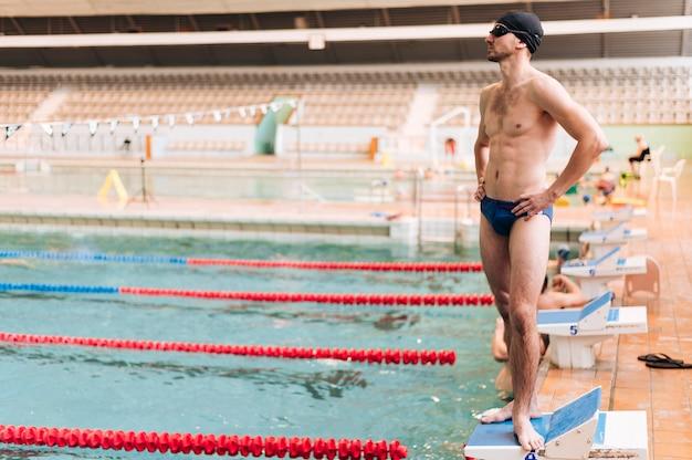 プールの端に立っている高角度の男性スイマー 無料写真
