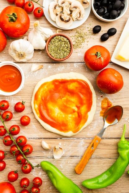 Выложить томатный соус на тесто для пиццы Бесплатные Фотографии