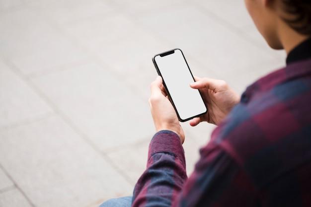Крупным планом мужчина держит телефон с макетом Бесплатные Фотографии
