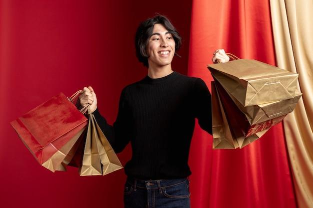 中国の新年のポーズの買い物袋を保持しているカジュアルな男 無料写真