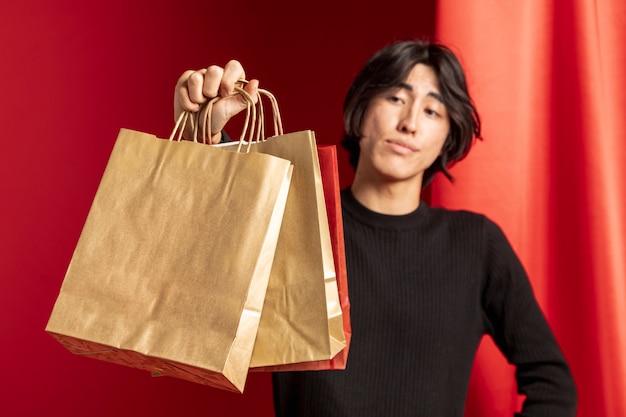 中国の新年の紙の買い物袋を示すカジュアルな男 無料写真