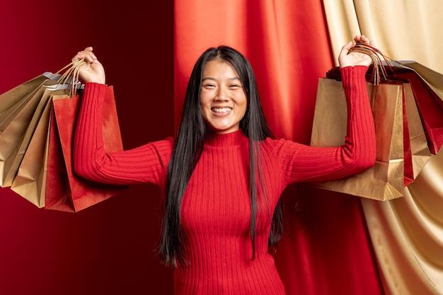カジュアルな女性が中国の新年の買い物袋でポーズ 無料写真