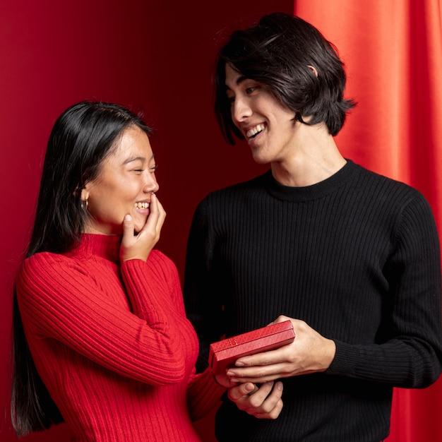 中国の新年の女性に贈り物を提供している男 無料写真
