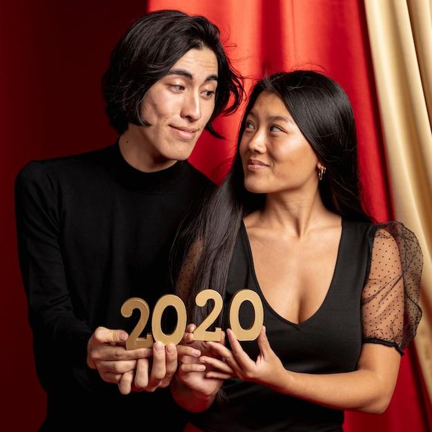 新年のサインを保持しているお互いを見てカップル 無料写真