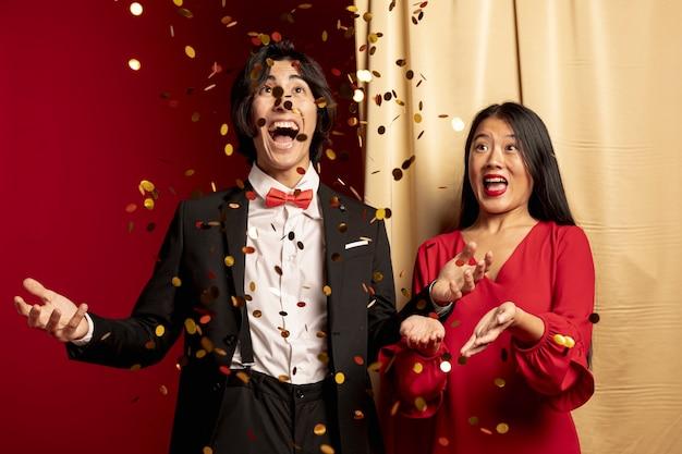 黄金の紙吹雪を投げて楽しんでいるカップル 無料写真