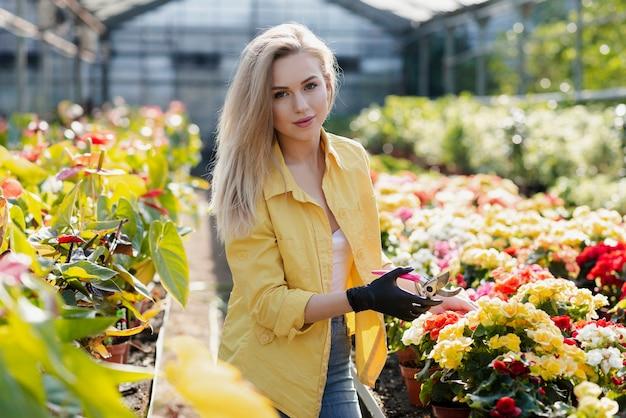 Портрет красивой женщины заботится о цветах Бесплатные Фотографии
