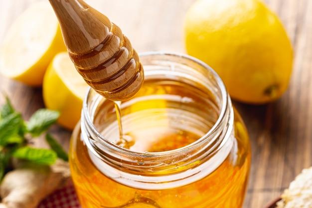 木製のひしゃくと蜂蜜の瓶 無料写真