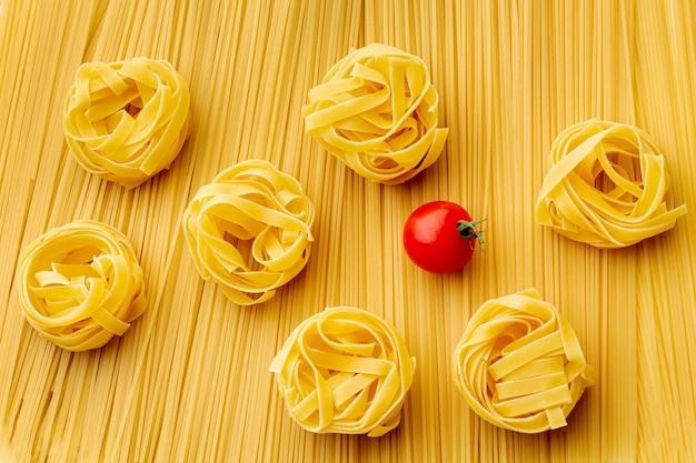 Плоские лежали сырые спагетти тальятелле и помидоры Бесплатные Фотографии