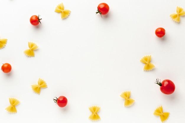コピースペースを持つトマトとフラットレイアウト未調理ファルファッレ配置 無料写真