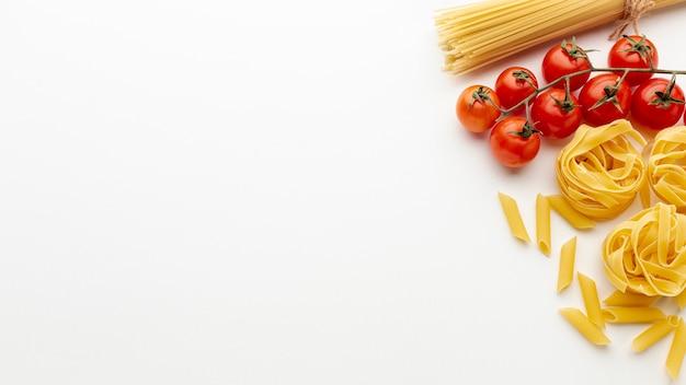 Сырые пенне тальятелле спагетти и помидоры с копией пространства Бесплатные Фотографии