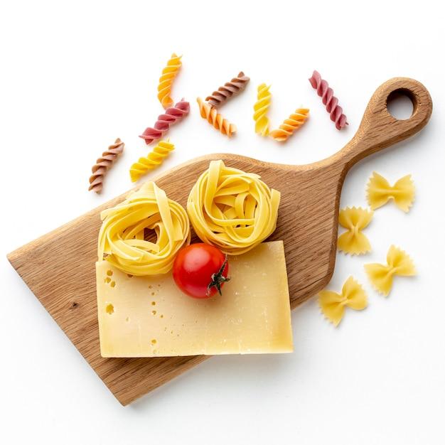 未調理のタリアテッレファルファッレフジッリ、ハードチーズとトマト添え 無料写真