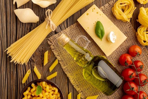 Сырую пасту смешать с помидорами, оливковым маслом и твердым сыром Бесплатные Фотографии