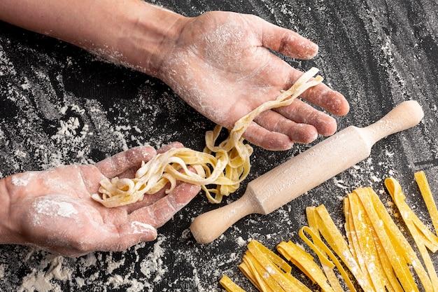 Шеф-повар делает макароны возле скалки Бесплатные Фотографии