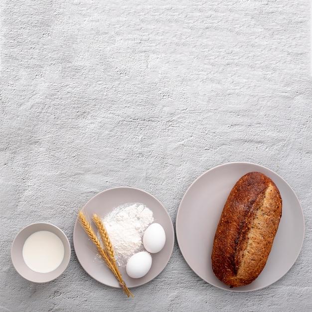 卵とコピースペースの背景にパンと様々なプレート 無料写真