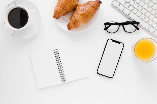 Круассан с блокнотом черного кофе и смартфоном Бесплатные Фотографии