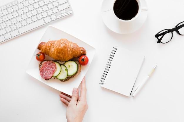 Рука держит тарелку с круассаном и бутербродом возле ноутбука Бесплатные Фотографии