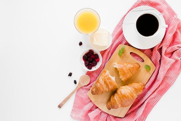 Круассаны на разделочной доске с кофе и апельсиновым соком Бесплатные Фотографии