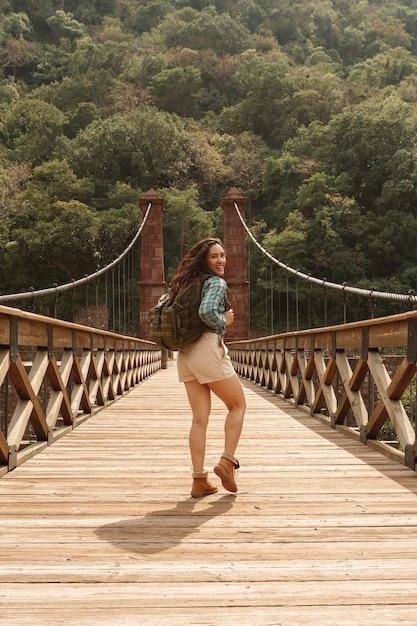 Женщина вид спереди с рюкзаком, оглядываясь назад Бесплатные Фотографии