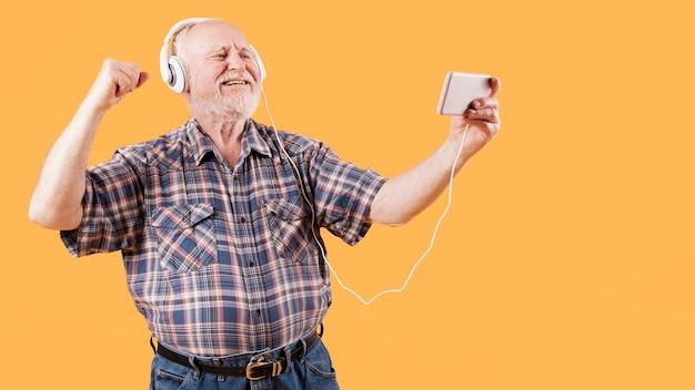電話でミュージックビデオを見て幸せな先輩 無料写真