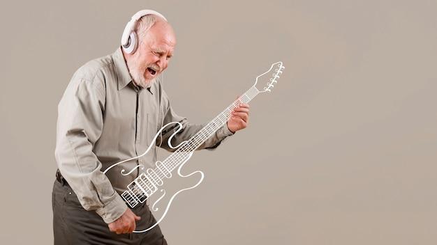 Возбужденный старший играет на воображаемой гитаре Бесплатные Фотографии