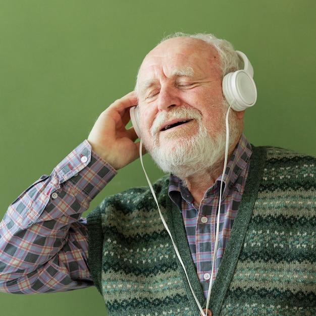 ヘッドフォンで音楽を楽しむシニア 無料写真
