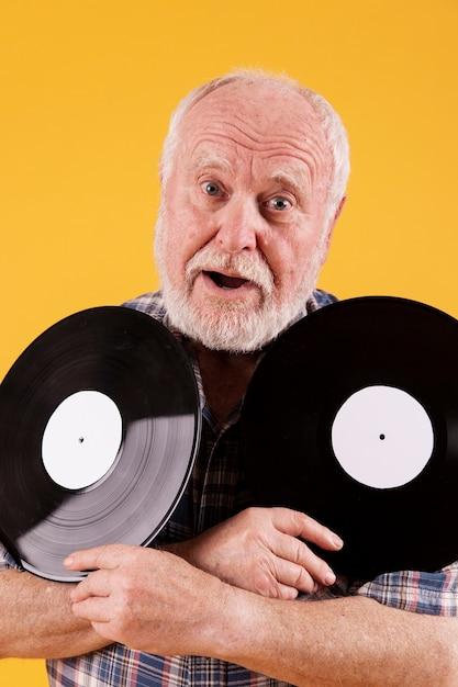 音楽レコードを保持している遊び心のあるシニア 無料写真
