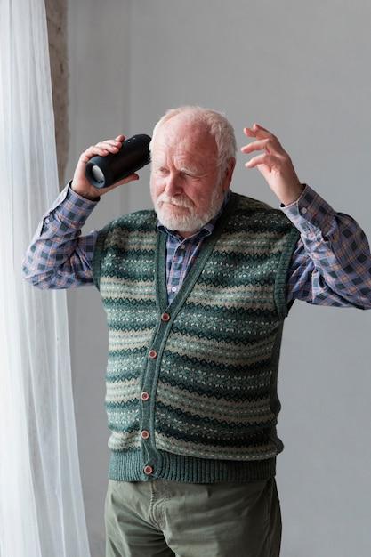 年配の男性がスピーカーで歌を再生 無料写真