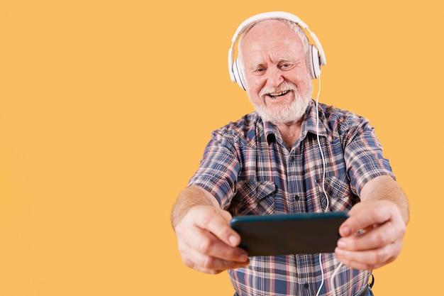 携帯電話で音楽を聴くローアングルスマイリーシニア 無料写真