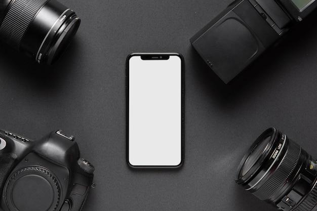 Концепция фотографии с аксессуарами камеры и смартфоном посередине Бесплатные Фотографии