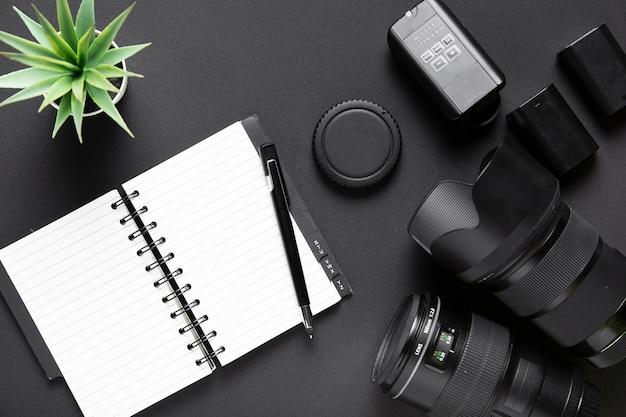 黒の背景にカメラアクセサリーとノートブックのトップビュー 無料写真