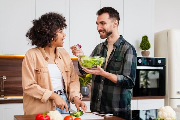 彼女のガールフレンドにサラダを提供している男 無料写真